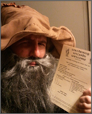"Hunter Davis dressed as a wizard, holding a copy of ""Wandering Wizards Welcome (By Appointment)."""